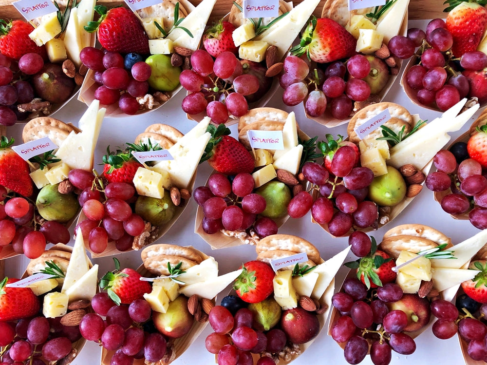 Individually-portioned cheese platters on bamboo grazing boats
