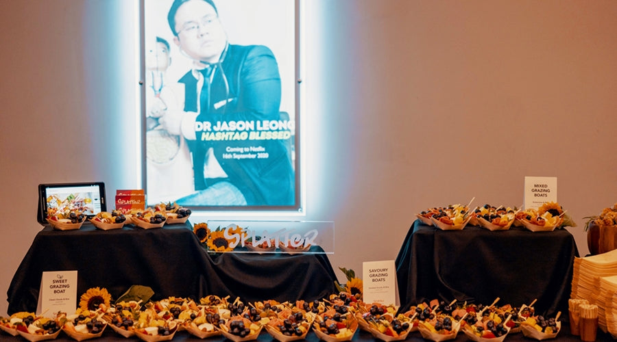 Grazing table spread with a poster of Dr Jason Leong's Netflix comedy special show, Hashtag Blessed, at the back.