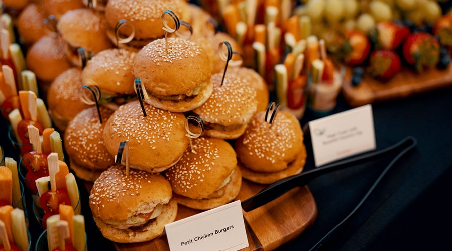 Table spread of petite chicken burgers stacked on wooden board, with a side of small clear cups filled with vegetable sticks