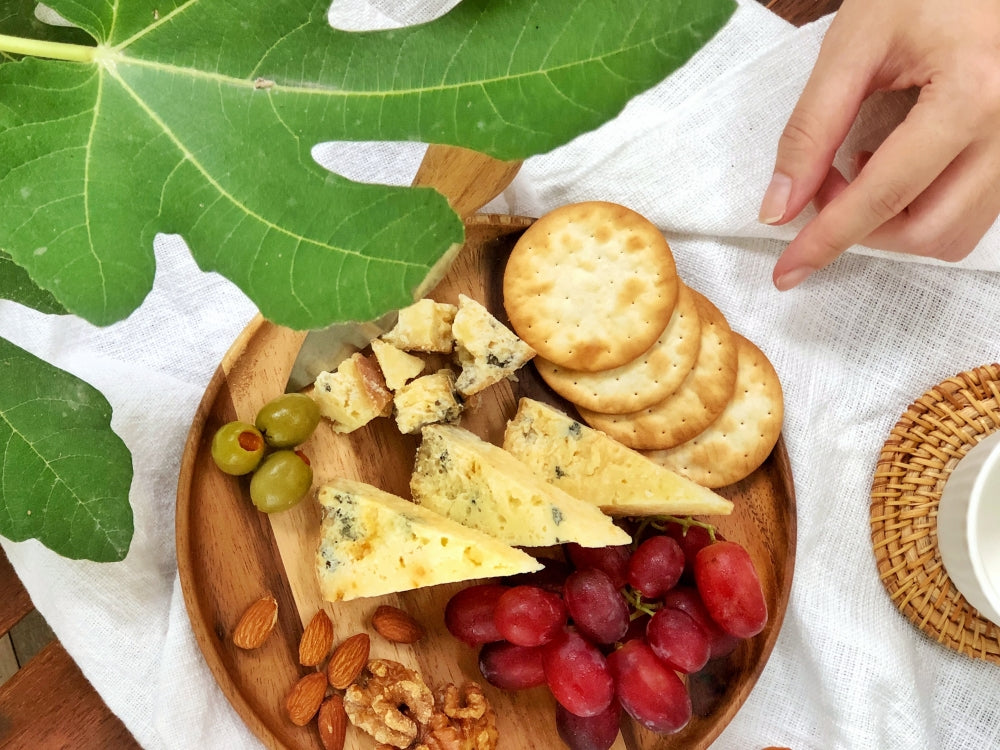 A hand reached out to a small cheese platter with Smoked Melaka cheese slices, grapes, crackers, nuts & olives.