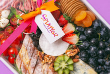 Load image into Gallery viewer, A close-up shot of Splatter's signature cheese platter covered with a transparent cover tied with pink and orange ribbons, with a white tag branded with Splatter logo. Cheese platter ingredients are visible through the cover.