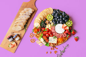 A colourful assortment of artisan cheeses, grapes, strawberries, kiwi, cherry tomatoes, dried apricots, turkey rolls, smoked salmon, nuts, crackers and sliced baguette arranged on a round wooden boards.