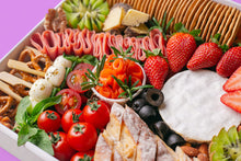 Load image into Gallery viewer, A close-up shot of the cheese platter in a white box, focusing on a round cheese wheel, fresh strawberries, cherry tomatoes, smoked salmon, turkey rolls, caprese salad skewers, and a row of water crackers.
