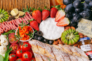 A colourful assortment of artisan cheeses, grapes, strawberries, kiwi, cherry tomatoes, dried apricots, turkey rolls, smoked salmon, nuts, and crackers that fills up the entire image.