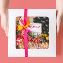 Load image into Gallery viewer, Splatter's Cheese & Meat Platter in a covered white box with transparent window that shows most of its content. Pink and orange ribbons form a knot in the middle with a tag branded with Splatter's logo. Two hands hold the side of the box.