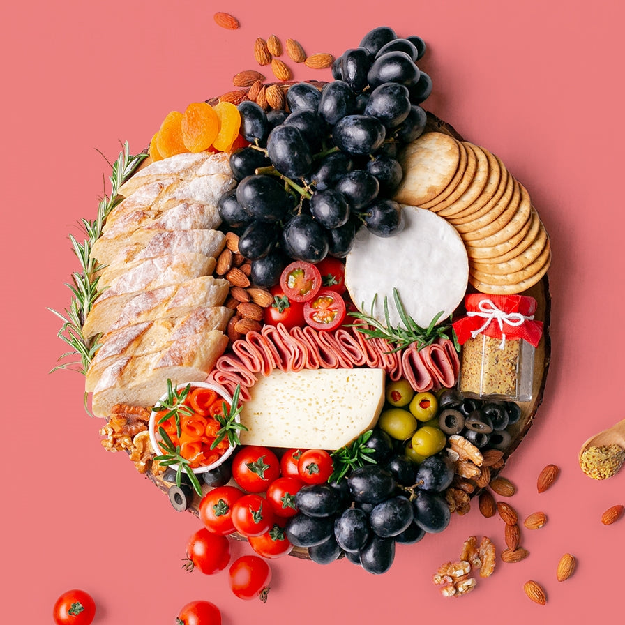 A round wooden board carries a platterful of soft cheese wheel and semi-firm cheese block accompanied by black grapes, cherry tomatoes, green olives, black olives, smoked salmon, turkey rolls, jar of wholegrain mustard, dried apricots, roasted almonds, walnuts, crackers, and baguette slices.