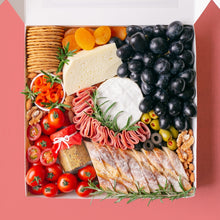 Load image into Gallery viewer, A white square box is packed to the brim with a soft cheese wheel and semi-firm cheese block accompanied by black grapes, cherry tomatoes, green olives, black olives, smoked salmon, turkey rolls, jar of wholegrain mustard, dried apricots, roasted almonds, walnuts, crackers, and baguette slices.