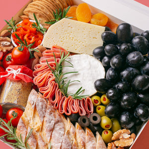 A white square box is packed to the brim with a soft cheese wheel and semi-firm cheese block accompanied by black grapes, cherry tomatoes, green olives, black olives, smoked salmon, turkey rolls, jar of wholegrain mustard, dried apricots, roasted almonds, walnuts, crackers, and baguette slices.