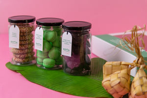 Splatter's Sekotak Riang Raya featuring 3 clear gift jars filled with cookies: Honey tahini, onde-onde macaron, triple dark chocolate chip cookies set on top of a banana leaf in a Raya & Ramadan theme.
