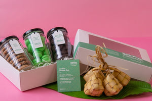 An opened Sekotak Riang Raya gift box with 3 cookie jars in it, each filled with honey tahini cookies, onde-onde macaron, triple dark chocolate chip cookies - framed by banana leaf, ketupat, and macarons for a festive Raya vibe.