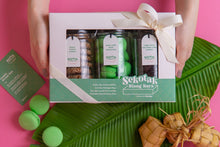Load image into Gallery viewer, A pair of hands hold a closed Sekotak Riang Raya gift box with 3 cookie jars in it, each filled with honey tahini cookies, onde-onde macaron, triple dark chocolate chip cookies - framed by banana leaf, ketupat, and macarons for a festive Raya vibe.