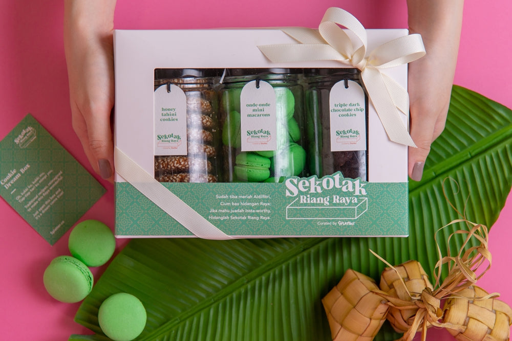 A pair of hands hold a closed Sekotak Riang Raya gift box with 3 cookie jars in it, each filled with honey tahini cookies, onde-onde macaron, triple dark chocolate chip cookies - framed by banana leaf, ketupat, and macarons for a festive Raya vibe.