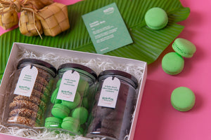 An opened Sekotak Riang Raya gift box with 3 cookie jars in it, each filled with honey tahini cookies, onde-onde macaron, triple dark chocolate chip cookies - framed by banana leaf, ketupat, and macarons at the back for a festive Raya vibe.