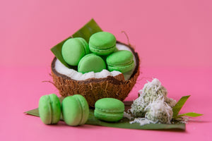 A handful of green onde-onde mini macarons stacked inside half a coconut shell, with a few kuih onde-onde on the side sitting on a banana leaf