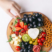 Load image into Gallery viewer, A hand reaches out to Splatter's cheese grazing platter on a round wooden board, topped with a small soft cheese wheel, gouda cheese cubes, grapes, strawberries, kiwi, cherry tomatoes, olives, turkey roll rose, mini pretzel crackers and roasted nuts.