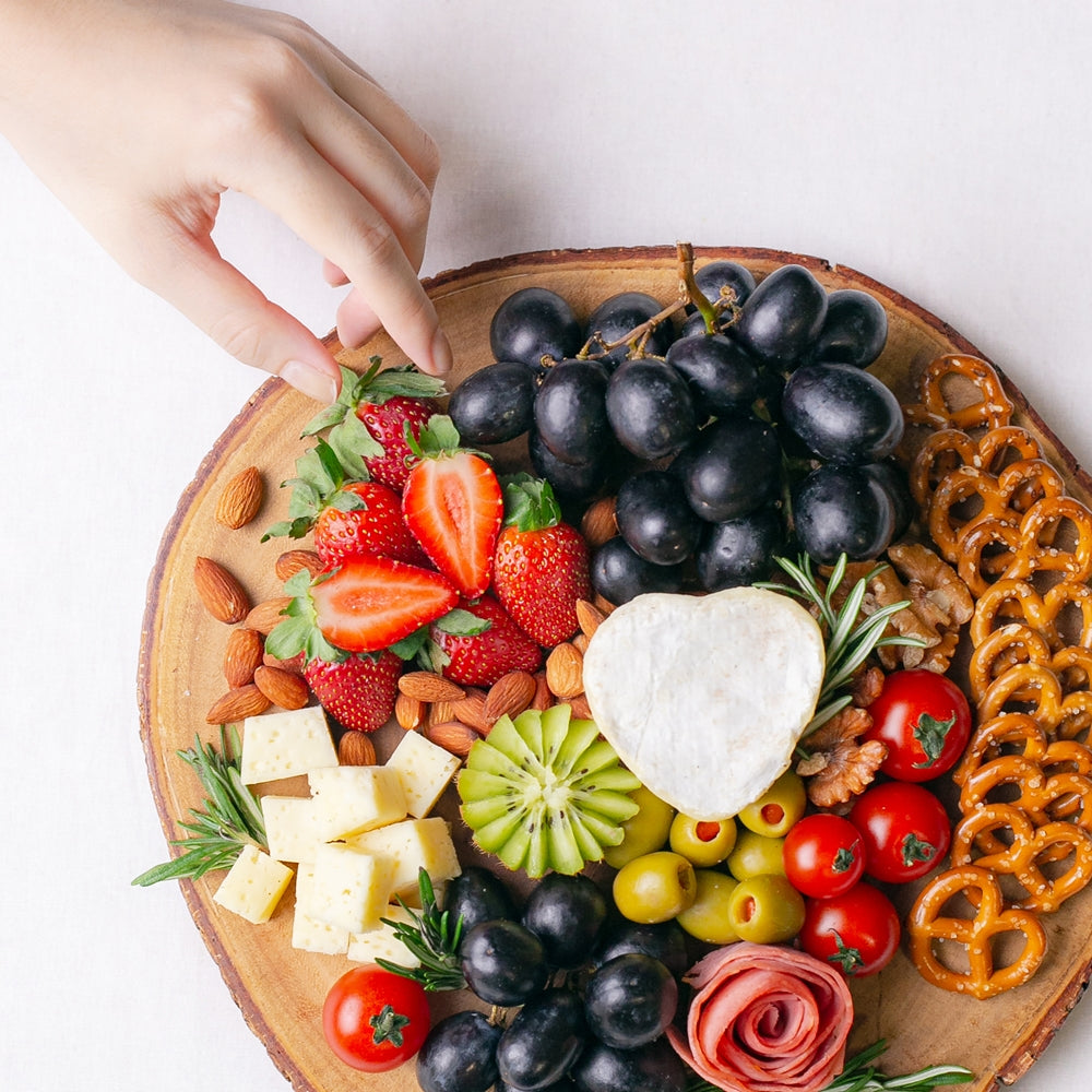 A hand reaches out to Splatter's cheese grazing platter on a round wooden board, topped with a small soft cheese wheel, gouda cheese cubes, grapes, strawberries, kiwi, cherry tomatoes, olives, turkey roll rose, mini pretzel crackers and roasted nuts.