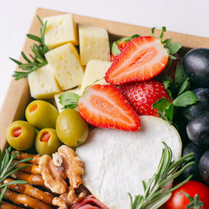 Close up of Splatter's mini cheese grazing platter box, filled to the brim with a small soft cheese wheel, gouda cheese cubes, grapes, strawberries, kiwi, cherry tomatoes, olives, turkey roll rose, mini pretzel crackers and roasted nuts.