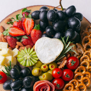 Close up of Splatter's cheese grazing platter on a round wooden board, topped with a small soft cheese wheel, gouda cheese cubes, grapes, strawberries, kiwi, cherry tomatoes, olives, turkey roll rose, mini pretzel crackers and roasted nuts.