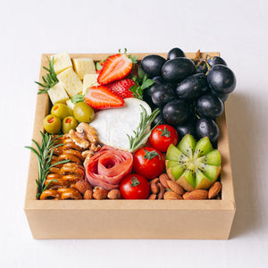 Splatter's mini cheese grazing platter box, filled to the brim with a small soft cheese wheel, gouda cheese cubes, grapes, strawberries, kiwi, cherry tomatoes, olives, turkey roll rose, mini pretzel crackers and roasted nuts.