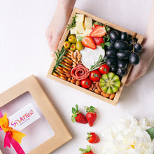 Load image into Gallery viewer, A pair of hands hold Splatter's mini cheese grazing platter box filled with a small soft cheese wheel, gouda cheese cubes, grapes, strawberries, kiwi, cherry tomatoes, olives, turkey roll rose, mini pretzel crackers and roasted nuts.