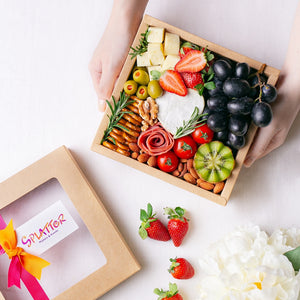A pair of hands hold Splatter's mini cheese grazing platter box filled with a small soft cheese wheel, gouda cheese cubes, grapes, strawberries, kiwi, cherry tomatoes, olives, turkey roll rose, mini pretzel crackers and roasted nuts.
