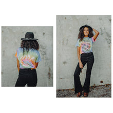 Load image into Gallery viewer, DoubleBlind: Woman poses with DoubleBlind Tie Dye Tee in front of a wall