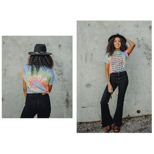 DoubleBlind: Woman poses with DoubleBlind Tie Dye Tee in front of a wall
