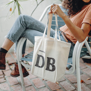 DoubleBlind: Woman sitting in chair holding the DoubleBlind Tote Bag.