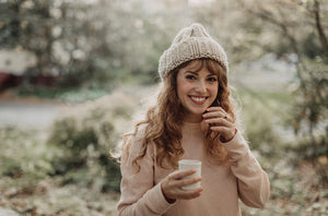Beautiful white woman with long auburn hair standing outside in pink shirt and winter hat smiling and holding a mug of hot beverage