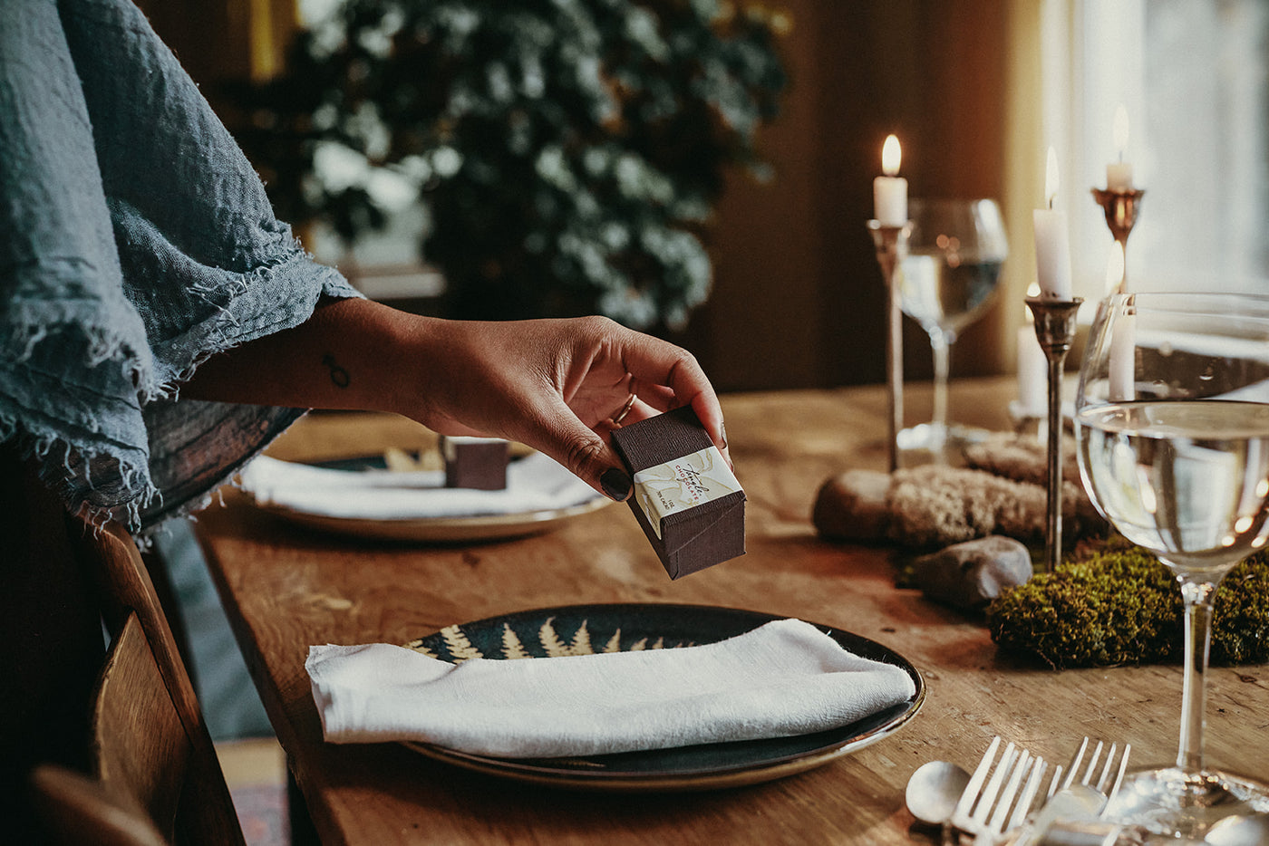 A Black woman's hand and arm holding a small box of Tangle Chocolate THINS, placing the box on a napkin as part of a beautiful table setting with candles, wood table, moss centerpiece.