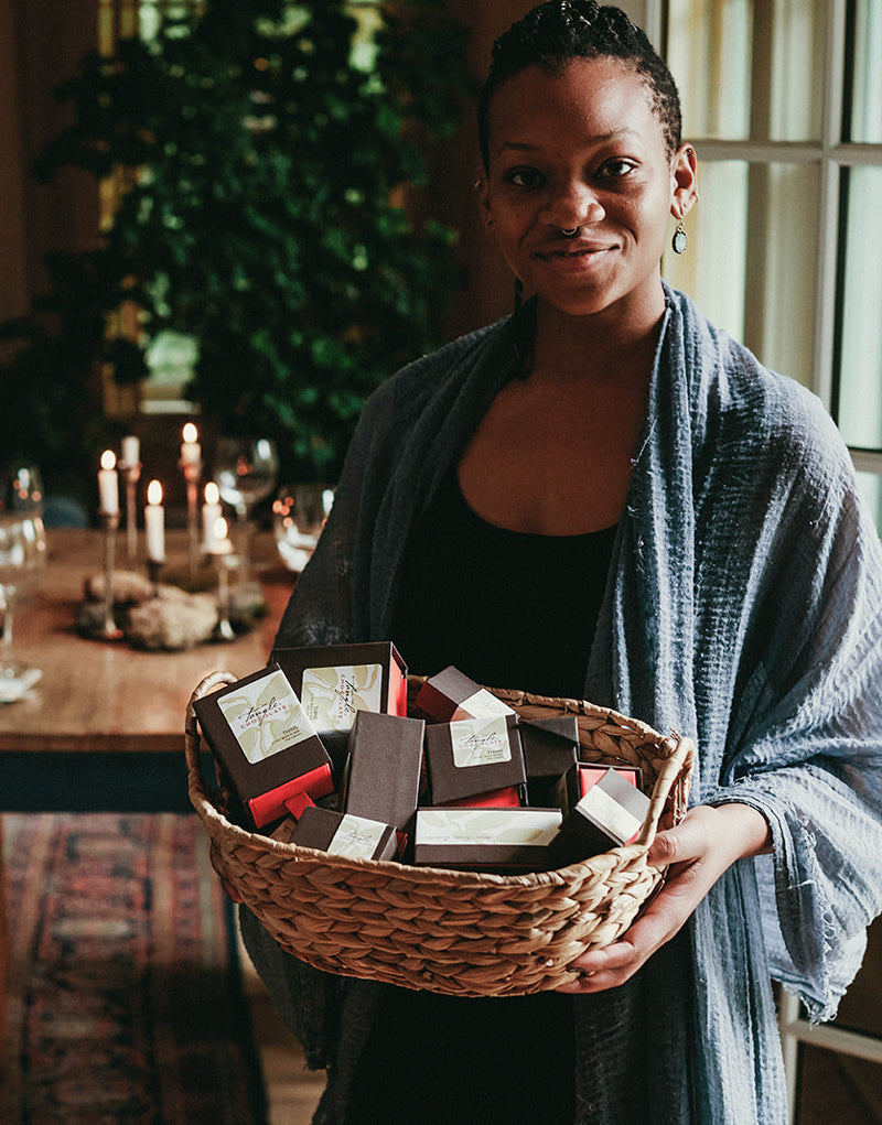 Beautiful Black woman smiling with blue shawl holding a basket filled with boxes of Tangle Chocolate, standing in front of a beautifully set dining room table with candles, warm colors, wood, and green plant in the background.