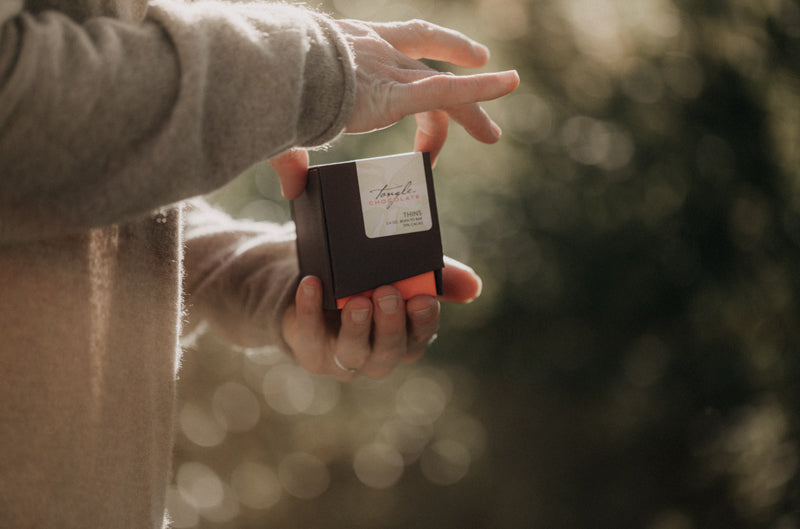 Hands holding a box of Tangle Chocolate THINS, brown box with white label and leaf pattern, coral accent, as though she's about to open the box. Outside setting, wearing a tan cashmere bathrobe.