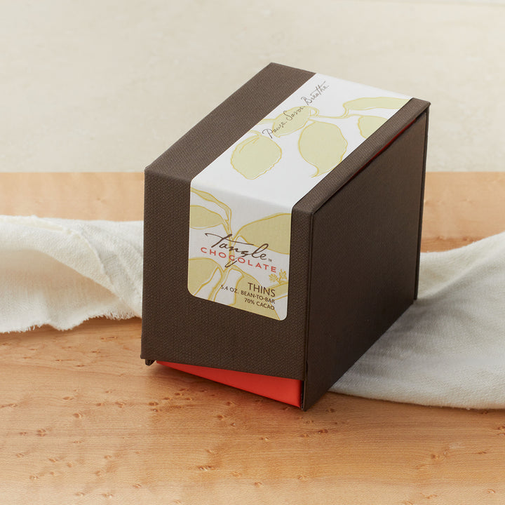 Large closed brown box with a coral accent and white, green, and gold label with leaf pattern that says Tangle Chocolate. on a maple table with a white cloth draped around it.