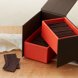Large open brown with dramatic coral inside with two layers of dark chocolate slivers, and two chocolate slivers lying next to the box. On a maple table with a white cloth draped around it.