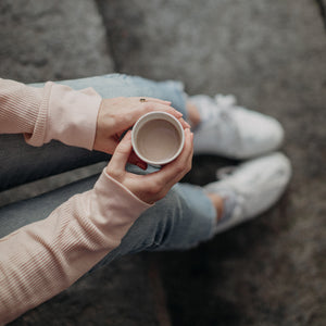 Photo taken from above looking down into a white mug of hot chocolate that is being held by someone whose head you can't see, only arms/hands holding the mug resting on legs in blue jeans and white sneakers, sitting on stone steps.