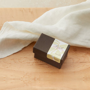 Small closed brown box with a hinged top and white/green/gold label with leaves that says Tangle Chocolate. On a maple table with a white cloth draped behind it.