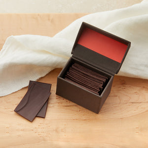 Small open brown box with a hinged top and coral color inside the lid. Filled with slivers of dark chocolate with a couple of the slivers to the side of the box. On a maple table with a white cloth draped behind it.