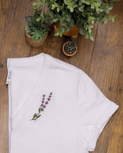 Load image into Gallery viewer, Wihte t-shirt with lavender embroidery on wood background