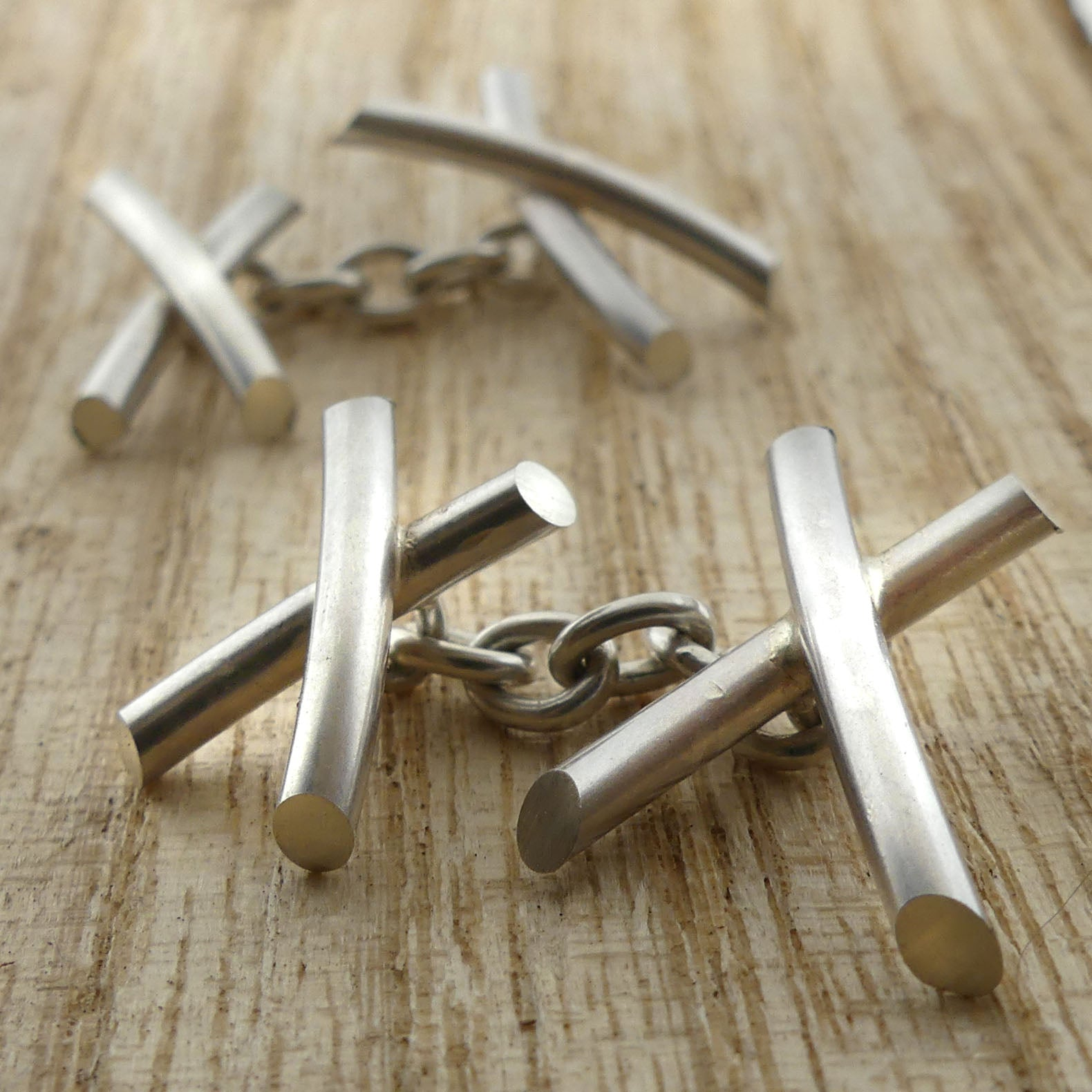Silver 'Kiss' cufflinks on wood