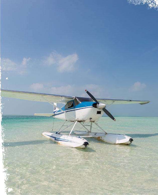 A seaplane floats in shallow water off the Key West coast