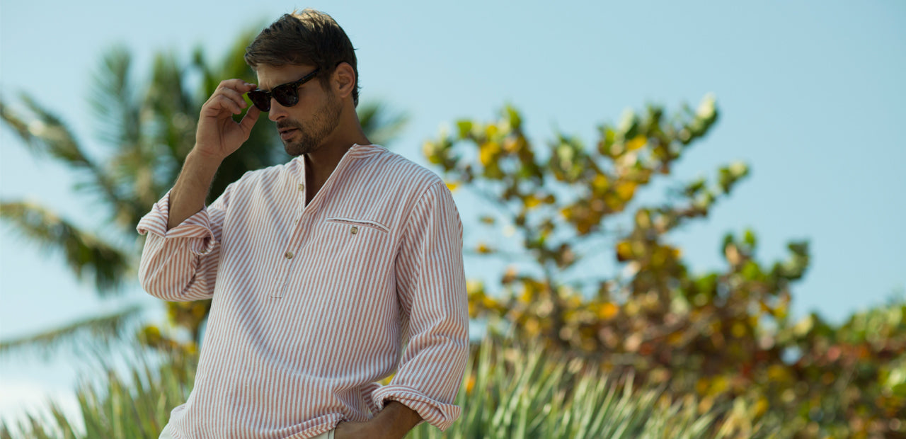 Castaway brand shirt in mineral red being worn by stylish man in sunglasses