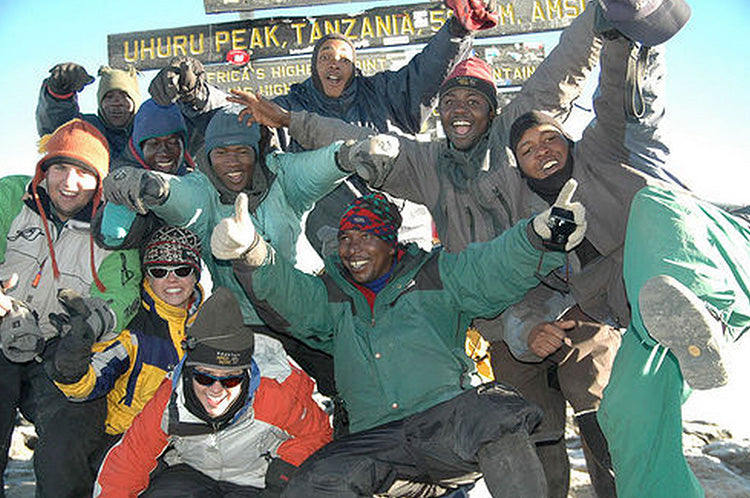 the group of climbers poses for a picture at the summit