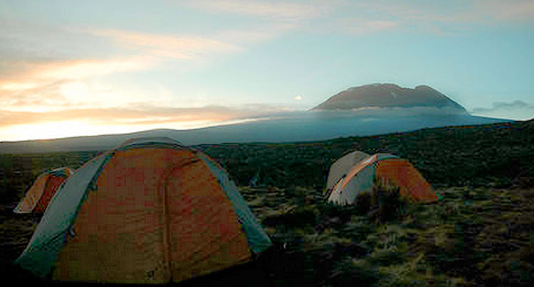 a group of tents on the mountain with a sunrise in the background