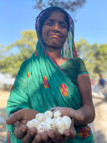 A picture of a native indian woman holding a handful of puffed makhana