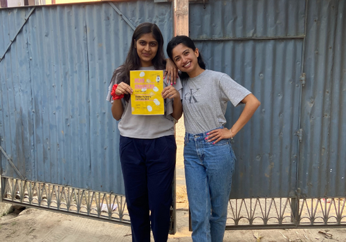 our founder, shifa and a friend holding a bag of golden turmeric makhana