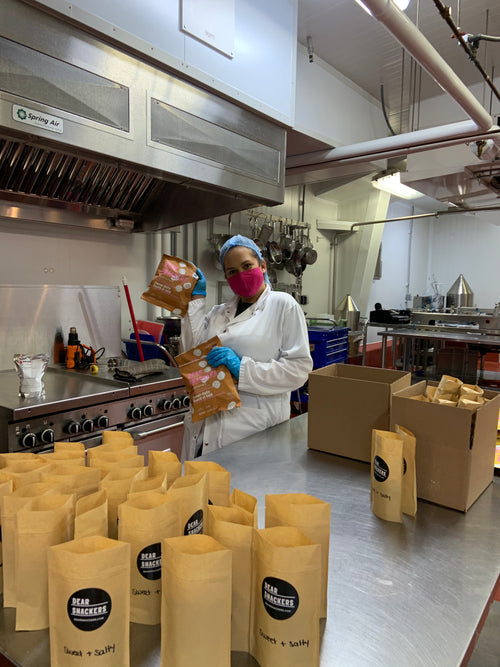 natasha in our flavour kitchen holding bags of freshly produced sweet and salty makhana, right here in canada