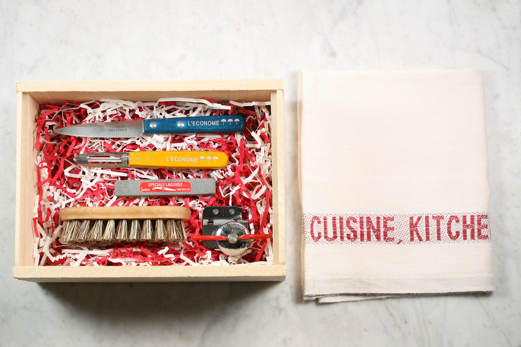 Wooden crate filled with colorful kitchen utensils.