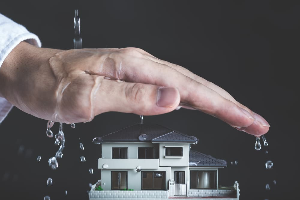 hand protecting small house from water