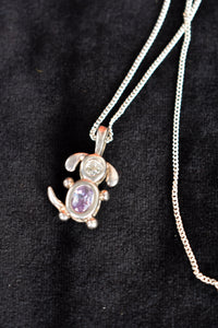 Dog pendant with purple jewel on chain
