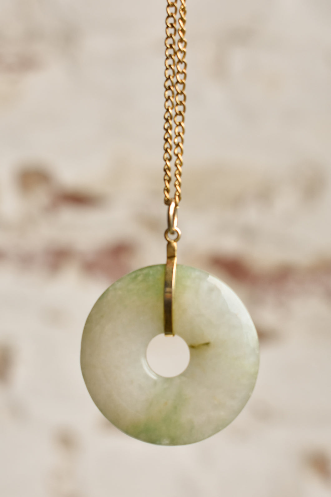Donut shaped stone pendant with gold coloured chain